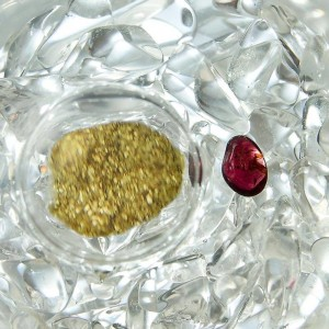 Gold flecks and a single maroon gemstone surrounded by clear crystals.